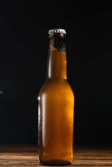 Close-up of a beer bottle on wooden desk