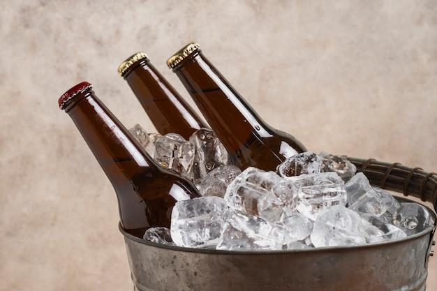 Бутылки пива крупным планом в кубиках холодного льда