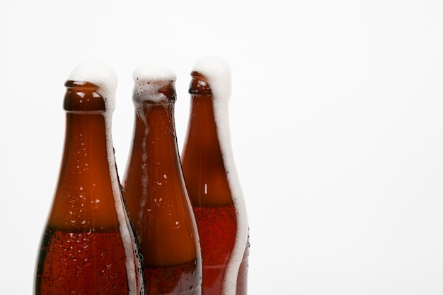 Close up beer bottles with foam and copy space