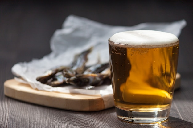 Close up. beer in glass and dried salt fish in the wooden background.