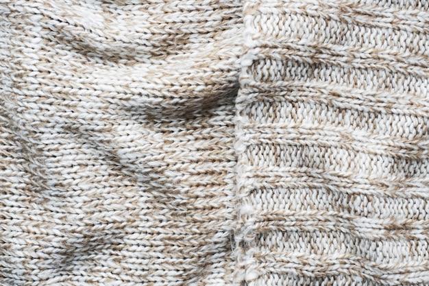 ナチュラルウールの風合いで編まれたベージュのセーターをクローズアップ