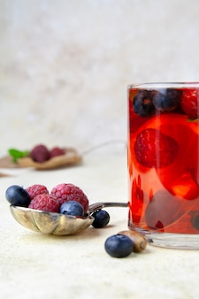 Close-up of berry tea and silver spoon