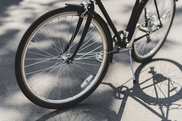 Close-up of bicycle parked on street in sunlight