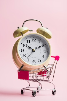 Close-up of big alarm clock on trolley over pink background