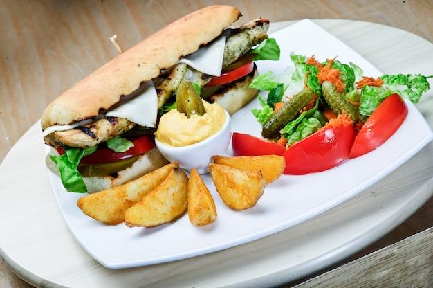 Закройте большой бургер с филе говядины с паниром, сыром и овощами на белой тарелке на сервированном столе в ресторане