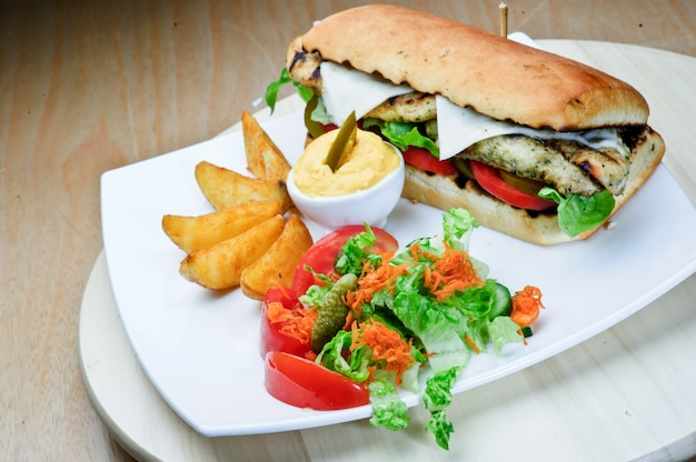 Закройте большой бургер с филе говядины с паниром, сыром и овощами на белой тарелке на столике в ресторане