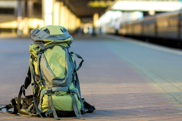 Close-up of big green tourist backpack on railway station platform. traveling, adventure and recreation concept.