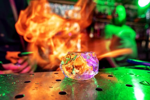 カクテルの準備のために火炎の準備でバーカウンターに氷の大きな溶けた部分をクローズアップ