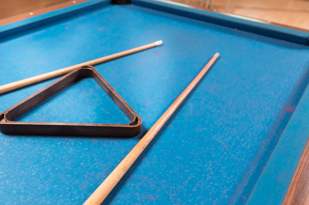 Close-up billiard table with cue sticks