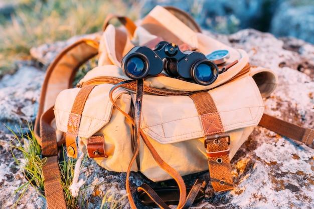 Close-up of binocular and bag on rock