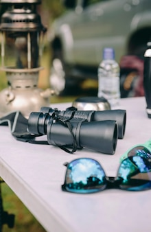 Close up of binoculars over camping table in a nature