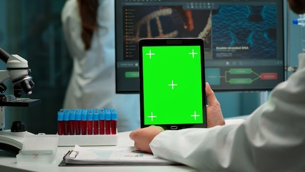 Close up of biochemist sitting at workplace in laboratory using green mock-up screen tablet with chroma key display. coworker working in background bringing blood sample.