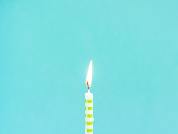 Close-up birthday candle on blue background