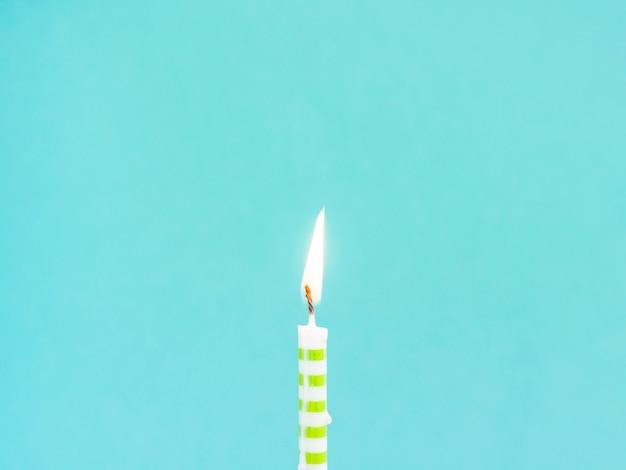 Candela di compleanno del primo piano su fondo blu