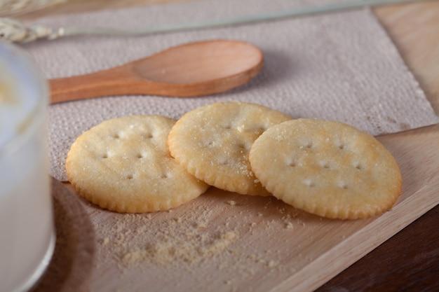 Закрыть печенье с горячим молоком на деревянной тарелке на деревянный стол на завтрак.