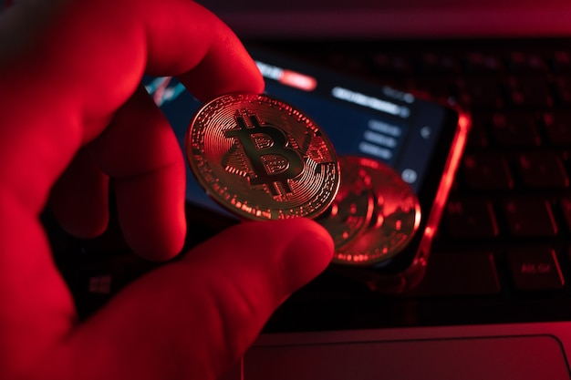 Close-up on bitcoin coin with red lighting alluding to falling coin, very short depth of field.