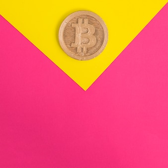Close-up of bitcoin on yellow and pink background