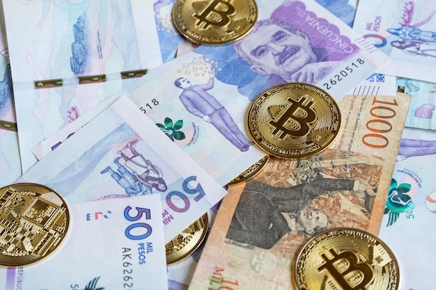 Close up of bitcoins over colombian banknotes