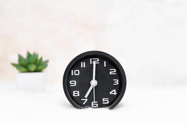 블랙 알람 시계와 테이블에 작은 장식 treein 꽃병을 닫습니다