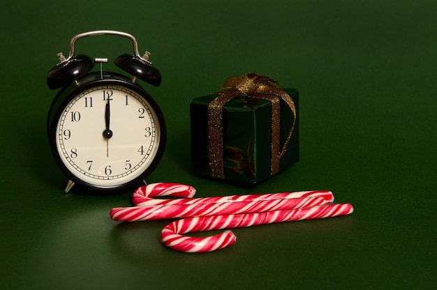 Close-up of black alarm clock with midnight on the dial, sweet striped lollipops, candy canes and christmas gift in glitter wrapping paper and golden bow isolated on green background with space for ad