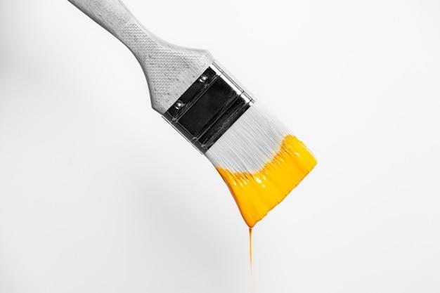 液体の黄色の絵の具がブラシから滴り落ちる絵筆の拡大白黒写真、コピースペース。