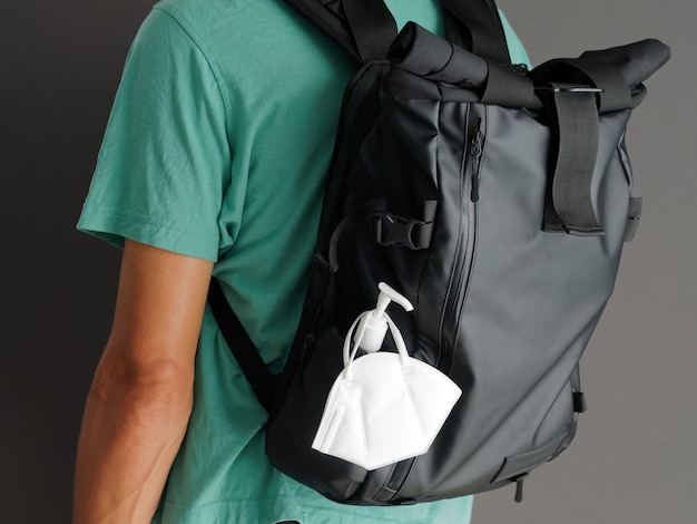 閉じる。男性の背中のポケットに消毒剤ボトルと保護フェイスマスクkn95が付いた黒いバックパック。