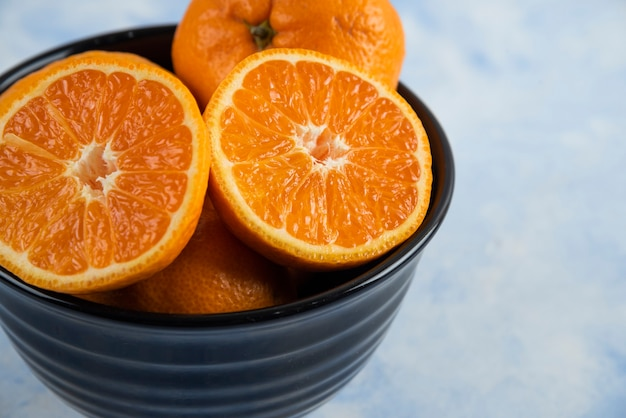 Close up of black bowl full with whole or half cut mandarins