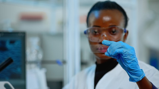 Close up of black chemistry doctor looking at virus test in equipped lab. african scientist working with various bacteria, tissue and blood samples, concept of pharmaceutical research for antibiotics