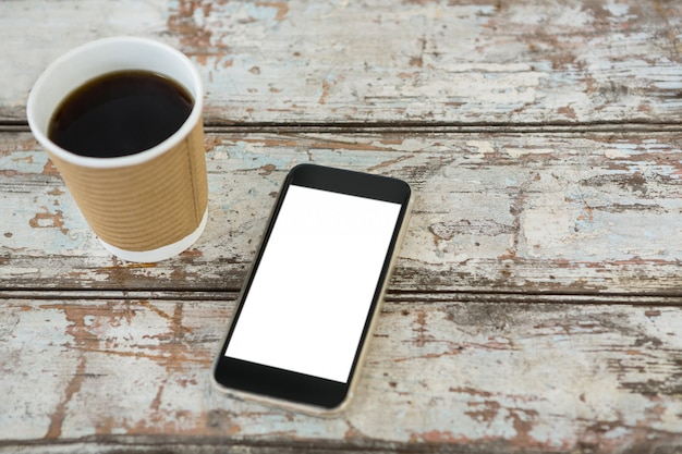 Close-up of black coffee and mobile phone