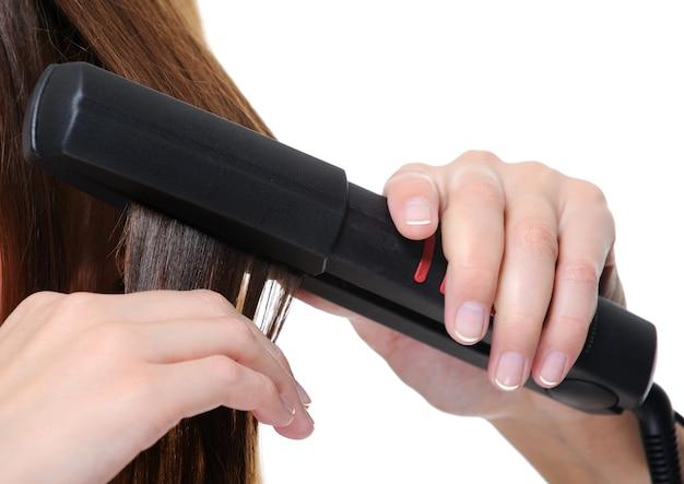 女性のブルネットの髪に適用するクローズアップの黒いフラットアイロン