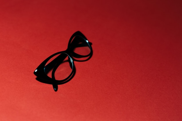 Close-up of black glasses on studio background of dark red color with copy space.