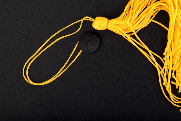Close-up black graduation cap and yellow tassel