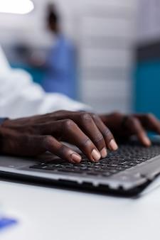 Primo piano delle mani nere che digitano sulla tastiera del laptop