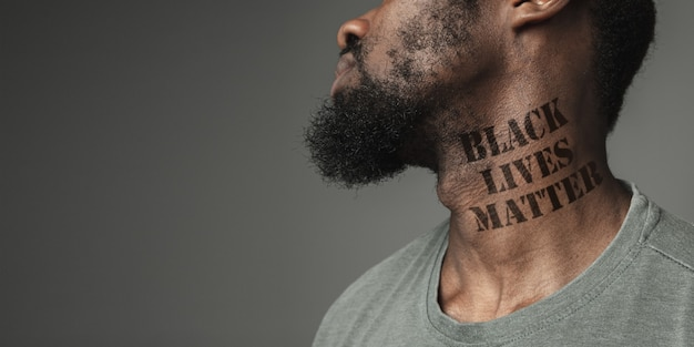 Close up black man tired of racial discrimination has tattooed slogan black lives matter