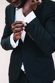 Close-up of a black man in a tuxedo fixing his cufflinks.groom bow tie cufflinks