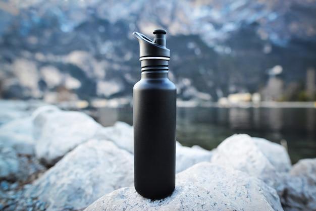 Крупным планом черный стальной эко термо бутылки с водой на фоне озера в горах.