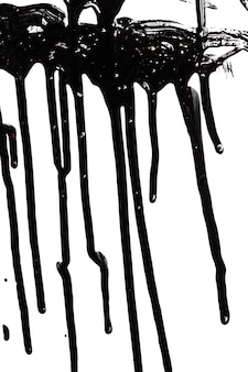 Close up of black paint leaking isolated on white background