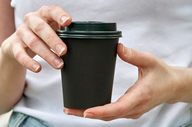 여자 손에 커피와 함께 근접 검은 종이 컵. 조롱