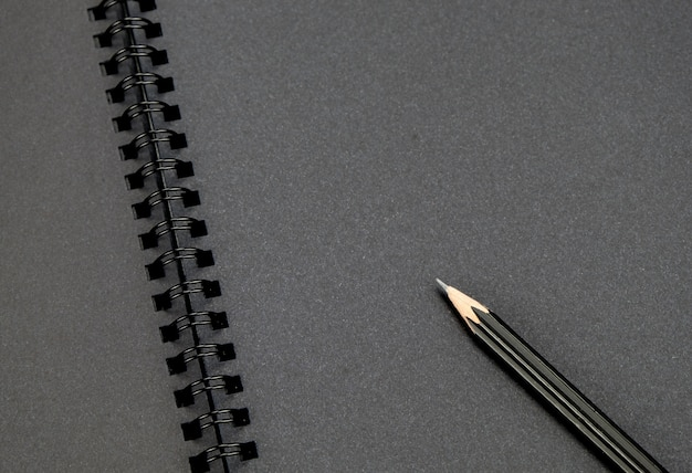 Close up at black pencil on blank black notebook