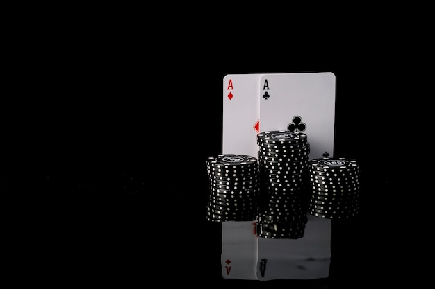 Close-up of black poker chips and two aces playing cards