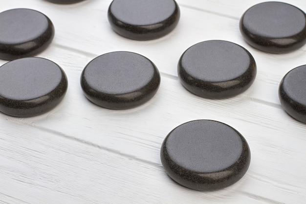 Крупным планом черные полированные круглые камни на белом деревянном столе. темные круглые магниты.