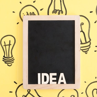 Close-up of a black slate with idea word on hand drawn light bulb background