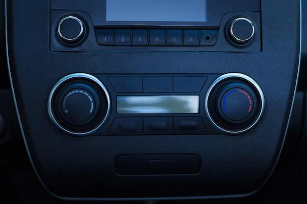 The close up of a black stylish head unit of a car with a stereo sound system being built in