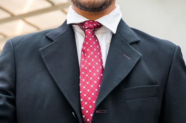 スマートビジネスマンの赤いネクタイとクローズアップ黒のスーツ