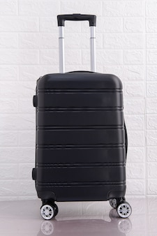Close up black suitcase  over brick wall minimal creative travel and transport concept.