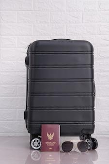 レンガの壁の上のタイのパスポートとサングラスで黒いスーツケースをクローズアップ最小限の創造的な旅行と輸送の概念。