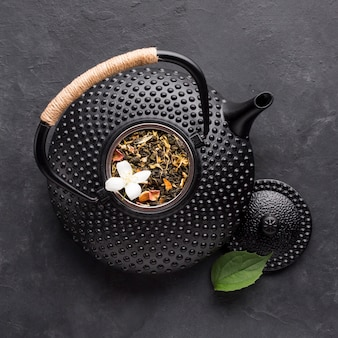 Close-up of black teapot with dried tea herb