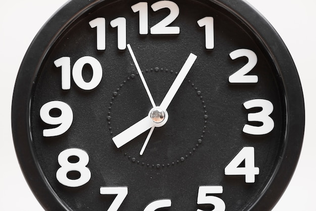 Close-up of a black wall clock face on white background