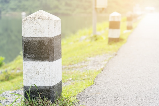 Close up of black and white milestone with green grass.