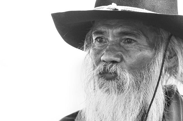 Close-up black and white photo of an old man in a cowboy costume